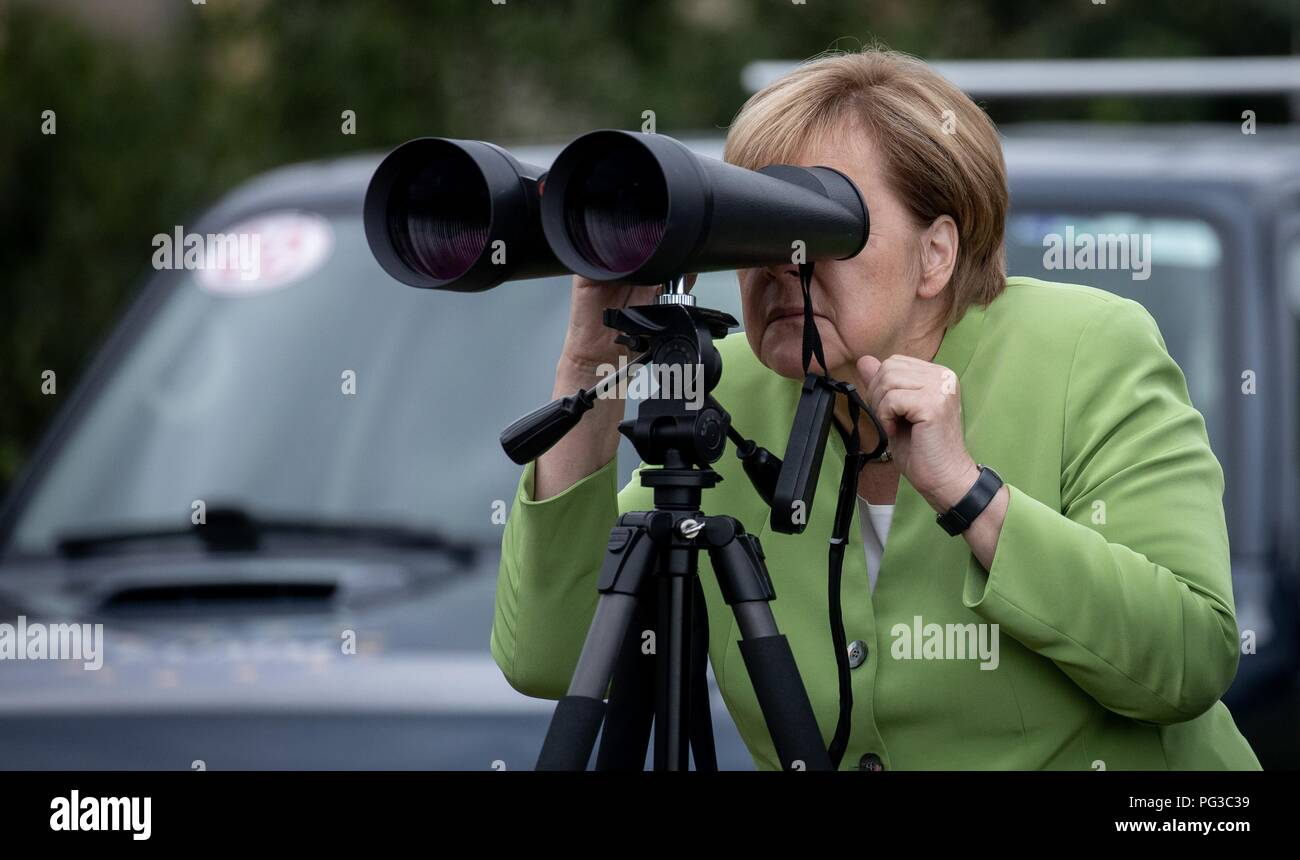 Odzisi, Georgia. 24th Aug, 2018. Federal Chancellor Angela Merkel (CDU) observes the administrative border line to Abkhazia and South Ossetia through binoculars next to the head of the European Monitoring Mission EUMM, Eric Hoeg. The Federal Chancellor will travel to the former Soviet Republics of Georgia, Armenia and Azerbaijan until 25 August 2018. Credit: Kay Nietfeld/dpa/Alamy Live News - Stock Image