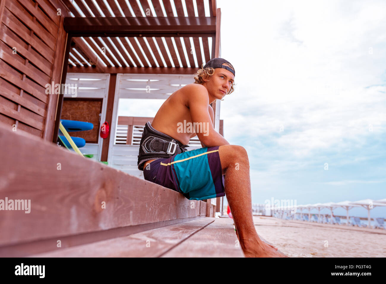 The surfer sits on the terrace on the beach and looking to the camera. Side view - Stock Image