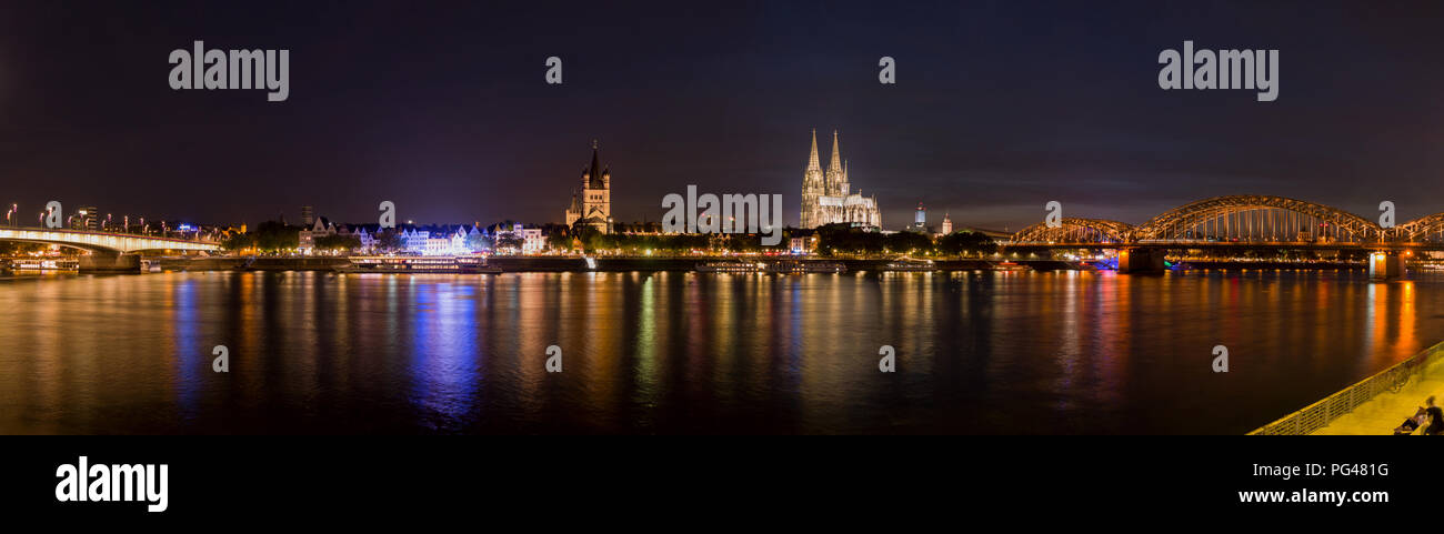 Wide Panorama of Cologne, Germany featuring Cathedral and bridge after sunset at blue hour panorama with river rhine in the foreground - Stock Image