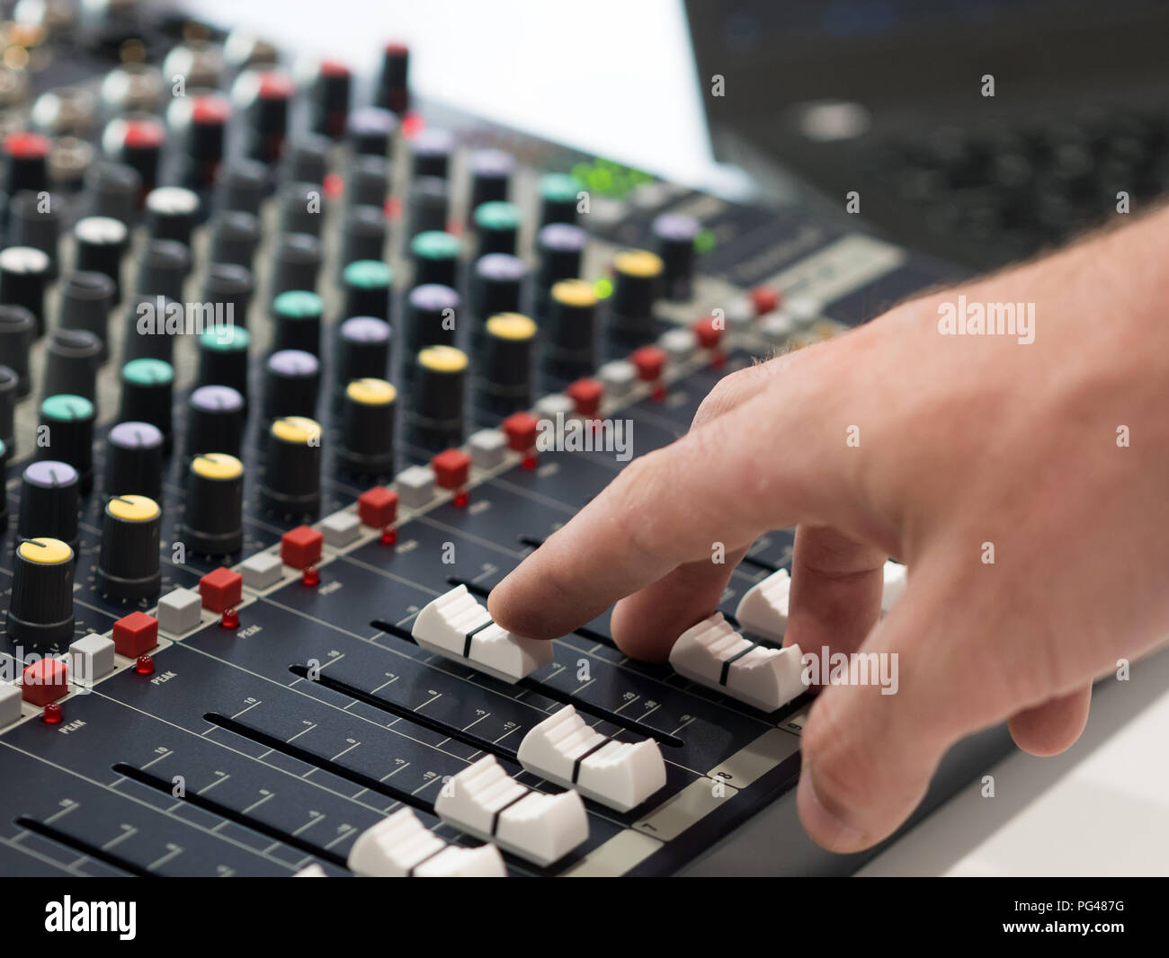 Audio engineer working on mixing console in music studio Stock Photo