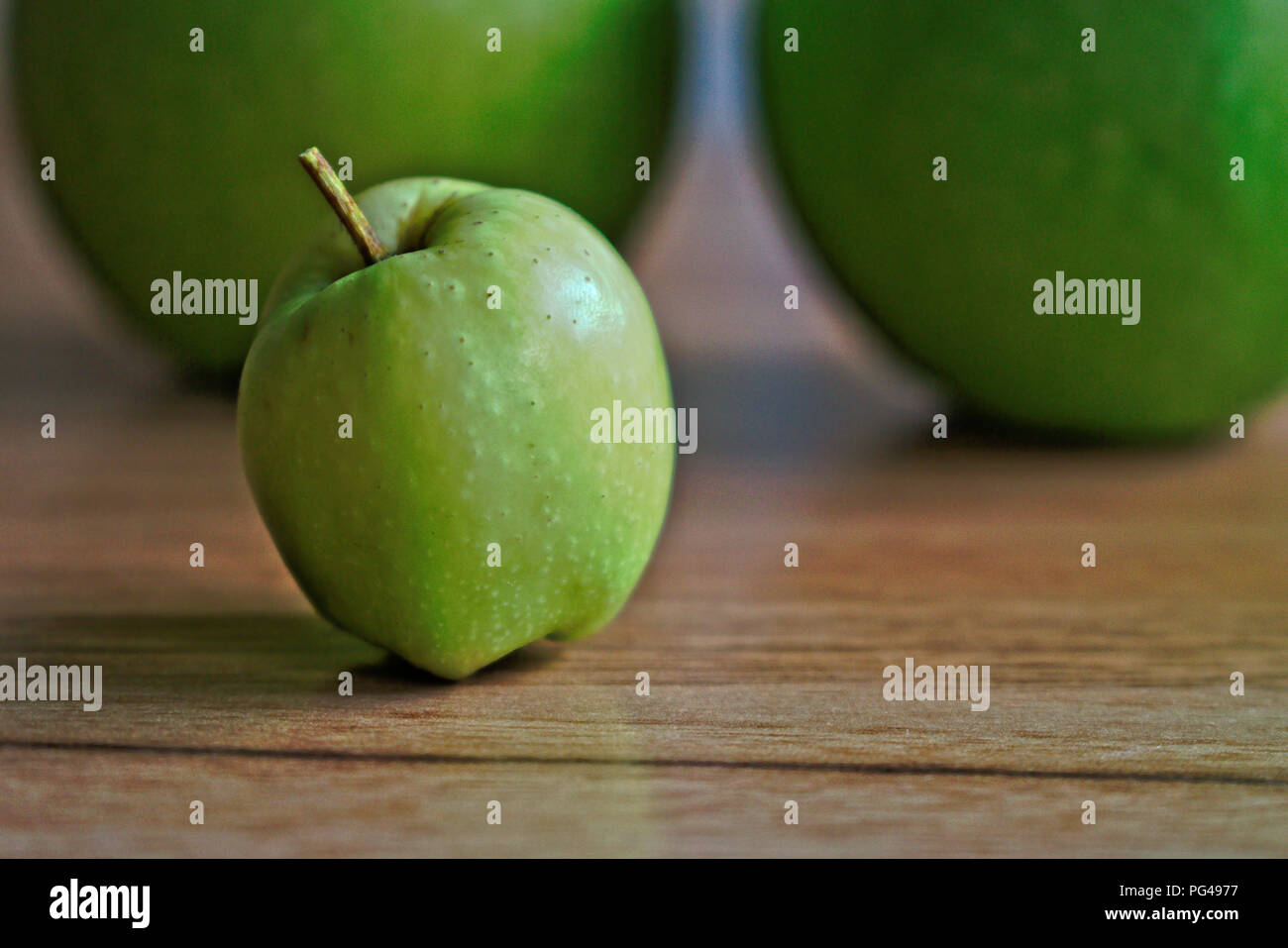 Closeup of green apples on a wooden table - Stock Image