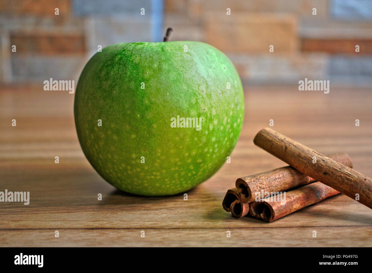 Green apple and cinnamon on a wooden table - Stock Image