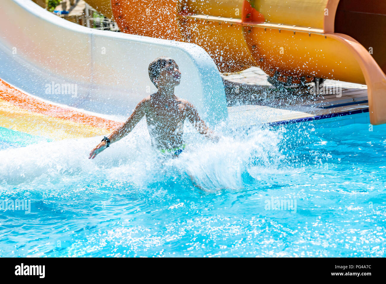 A happy boy on water slide in a swimming pool having fun during summer vacation in a beautiful aqua park. A boy slithering down the water slide and making splashes. - Stock Image