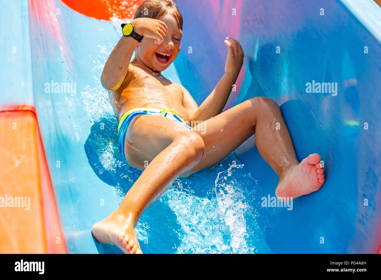 A happy boy on water slide in a swimming pool having fun during summer vacation in a beautiful aqua park. A boy slithering down the water slide and making splashes. Stock Photo