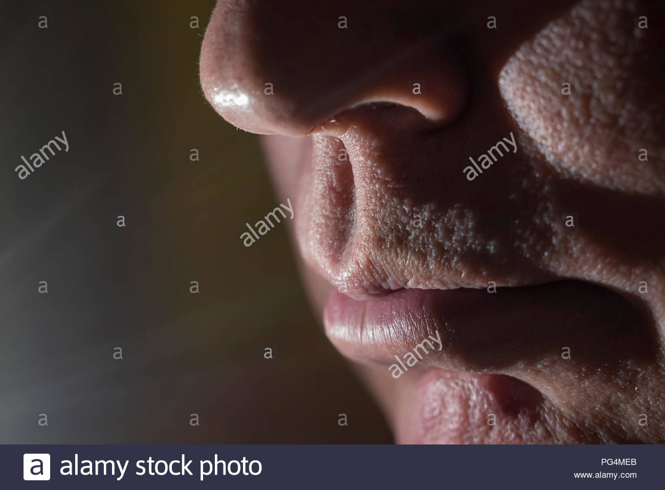 Closeup of middle aged mans face showing his mouth and nose, with moody lighting. Mood concept. Depressed. Depression. Creative lighting. Human senses. - Stock Image
