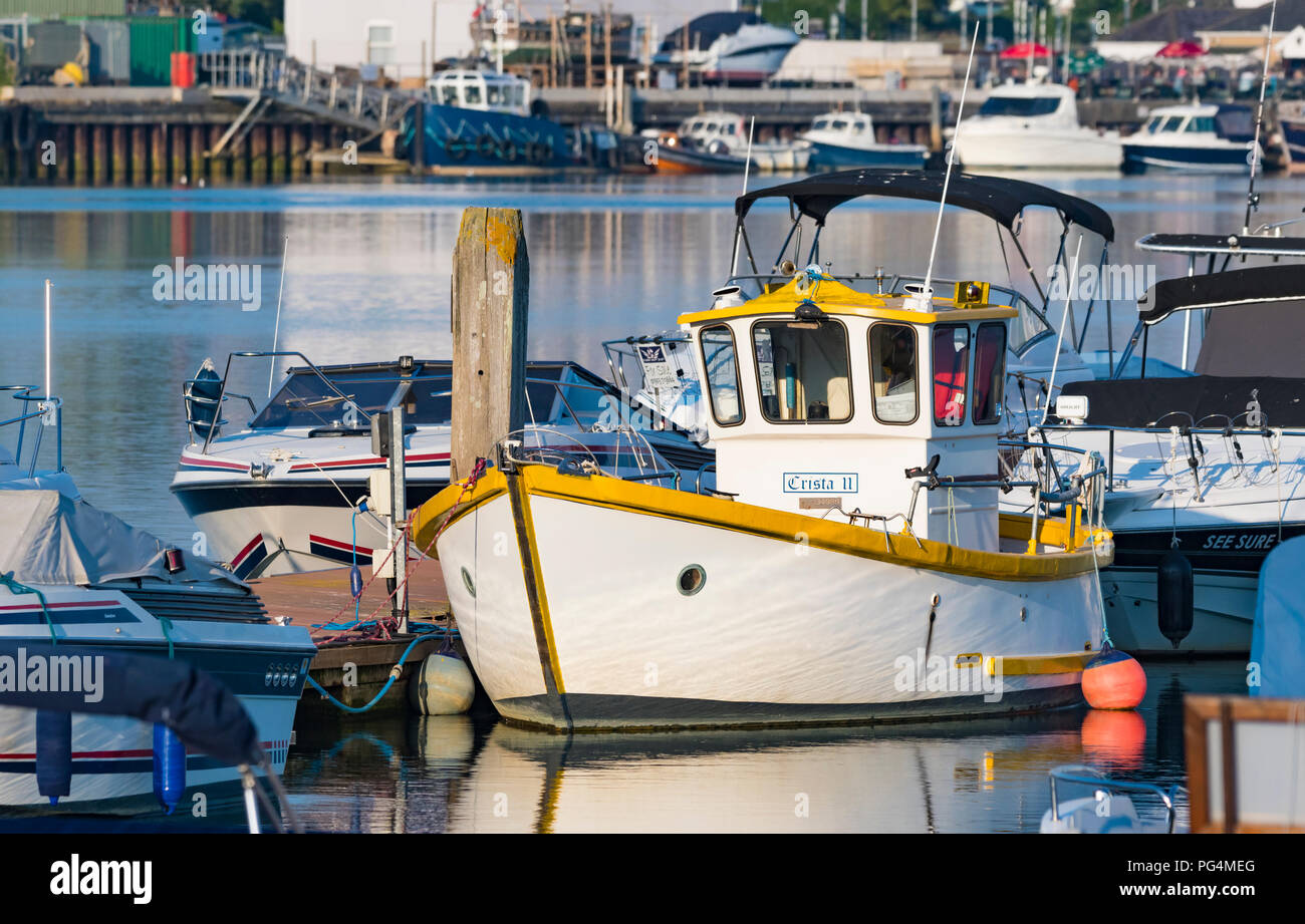 Small boat tied to a pontoon in a marina on a river in evening light in the UK. - Stock Image