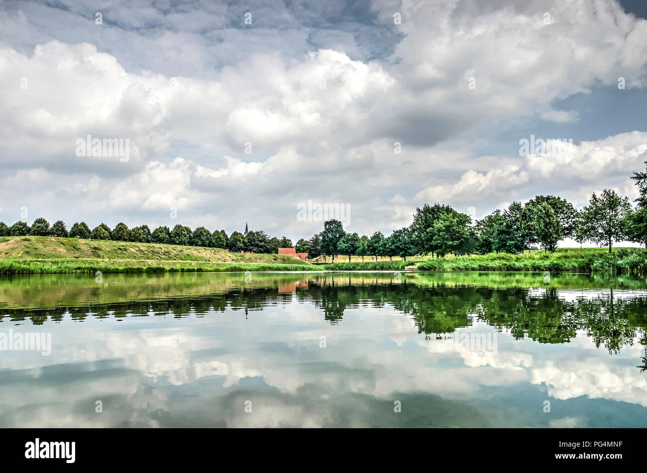 Dramatic cloudy sky reflecting in the calm water of one of the moats surrounding the fortified town of Leusden, The Netherlands - Stock Image