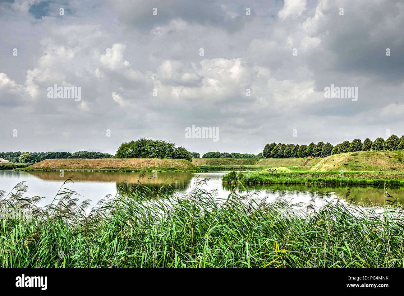 View across a bank with reeds towards the moats and ramparts around the fortified town of Leusden, The Netherlands - Stock Image
