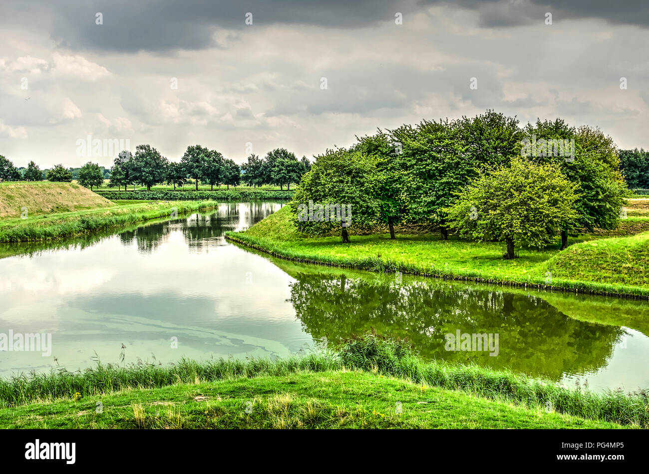 View from the ramparts of the fortified town of Leusden, The Netherlands towards a group of rees reflecting in one of the surrounding moats - Stock Image