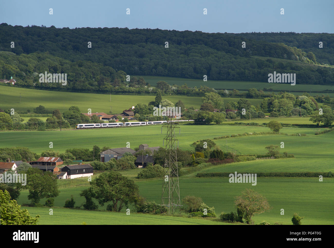 A trio of Chiltern Railways Class 168 Clubman DMUs heads north through the Chiltern Hills in Buckinghamshire, seen from Lodge Hill near Saunderton. - Stock Image