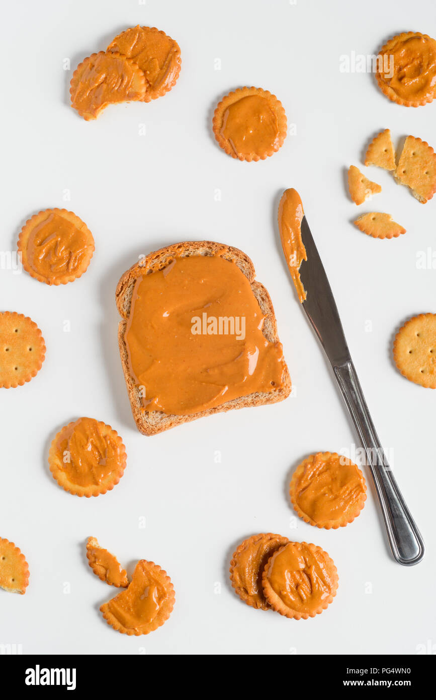 Whole grain peanur butter sandwich, close-up. Crackers, knife, white background. Stock Photo