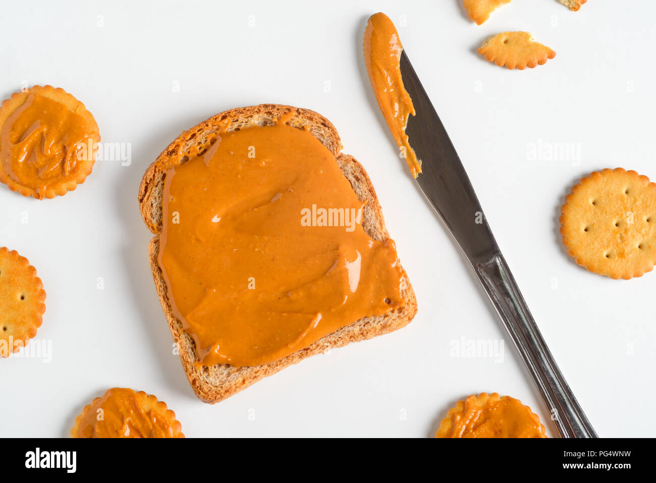 Whole wheat peanut butter sandwich, close-up. Knife, crackers, white background. Stock Photo