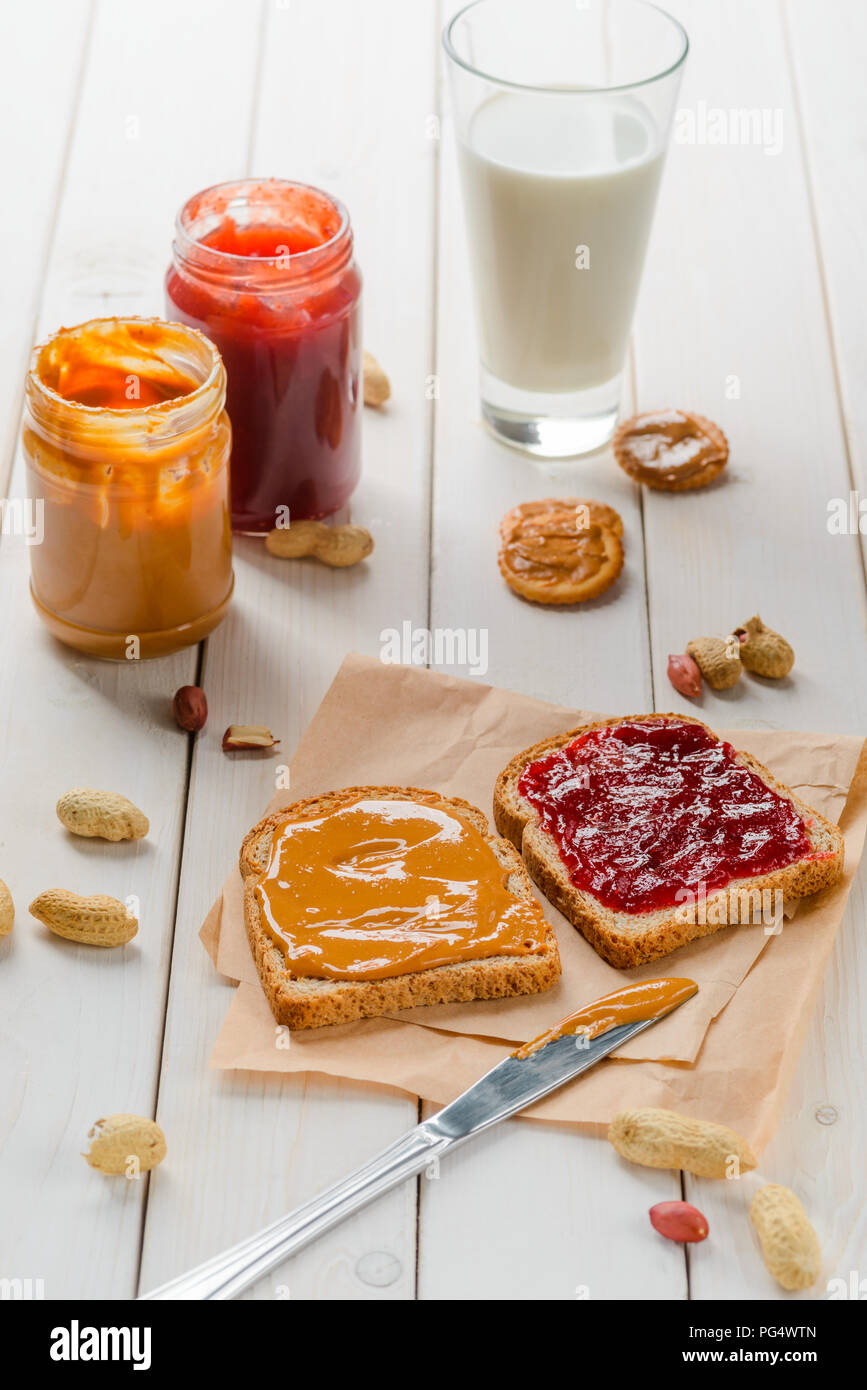 Glass of milk, jam and peanut butter sandwich, jars and crackers. Light wooden background. - Stock Image
