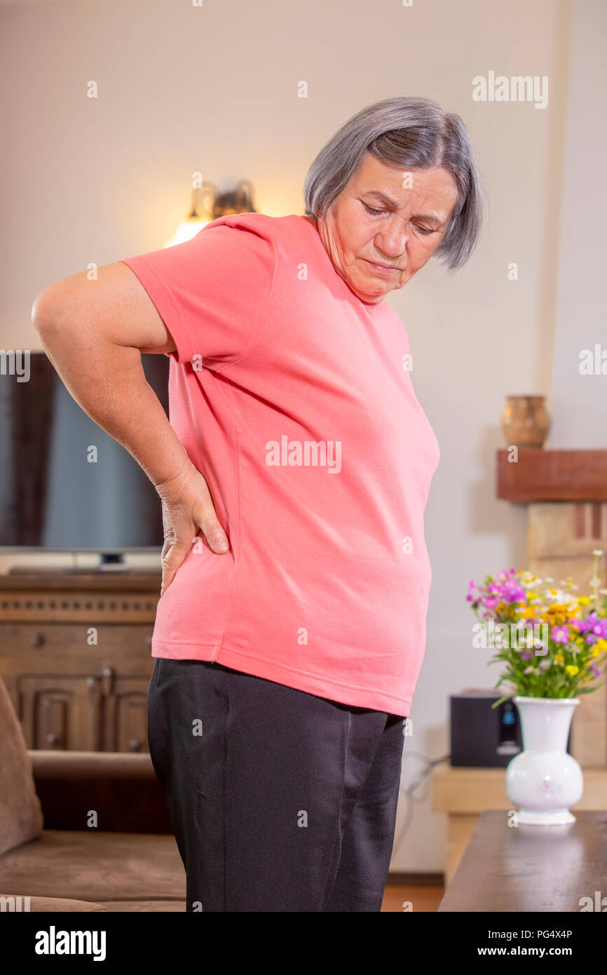Mature woman suffering from backache at home. Massaging lower back with hand, feeling exhausted, standing in living room. - Stock Image