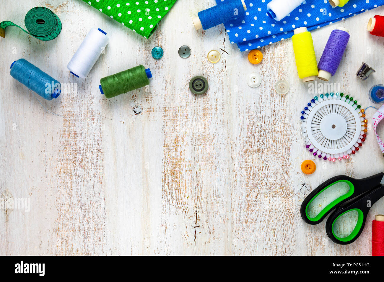 ed0cb7ac4d Sewing accessories and fabrics on a wooden background. Fabrics, measuring  tape, pins, buttons and thread.