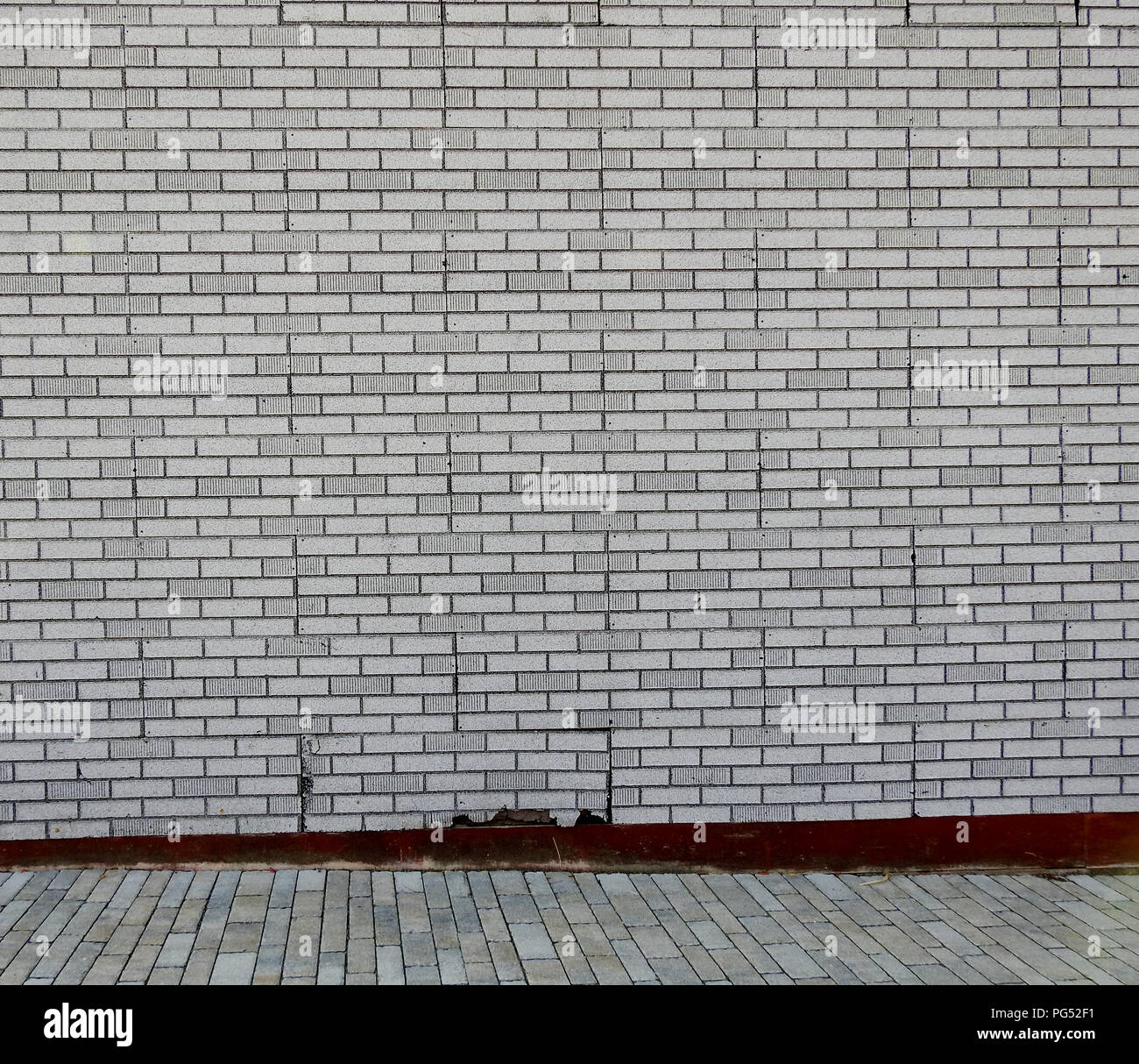 Sidewalk in front of a brick wall - Stock Image