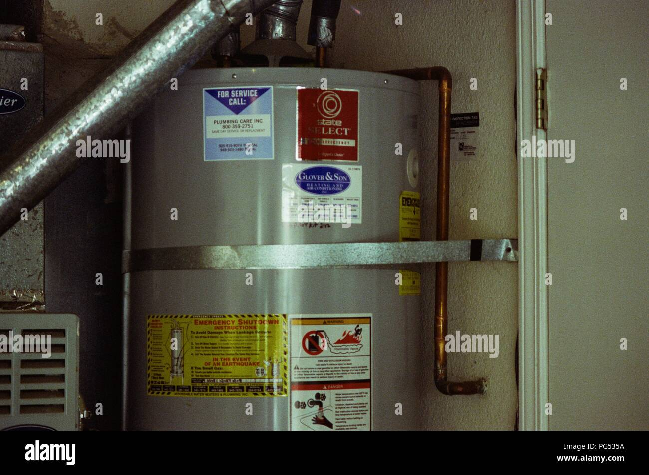 In the San Francisco Bay Area, a seismically active location, a residential hot water heater is connected to the wall using a metal tie-down to prevent the appliance from toppling over in the event of an earthquake, San Ramon, California, March 5, 2018. () - Stock Image