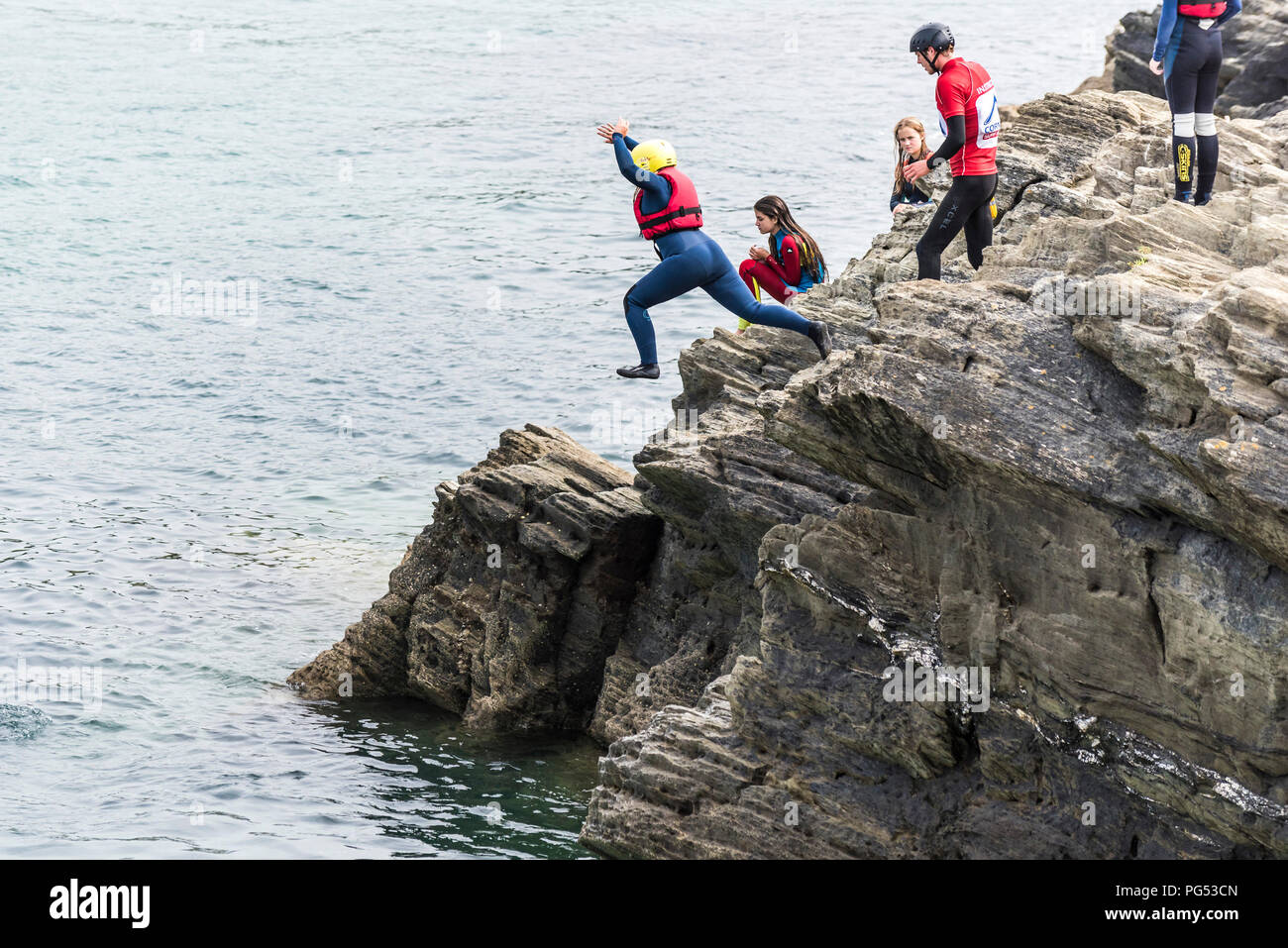 Holidaymakers coasteering on The Headland in Newquay, Cornwall. - Stock Image