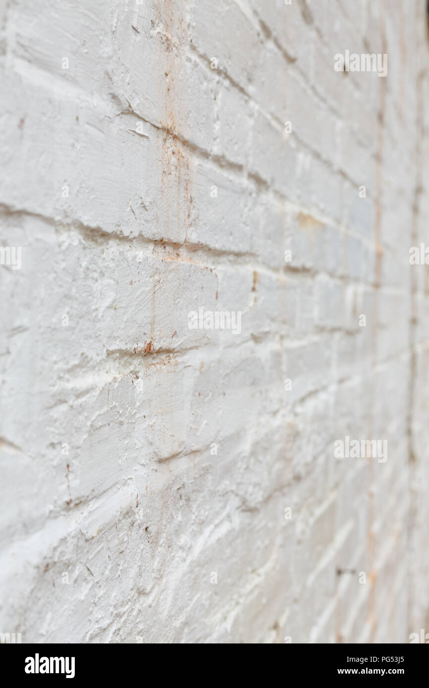 Detail of old brick wall painted white and distressed, peeling and stained. Ideal for grunge background texture Stock Photo