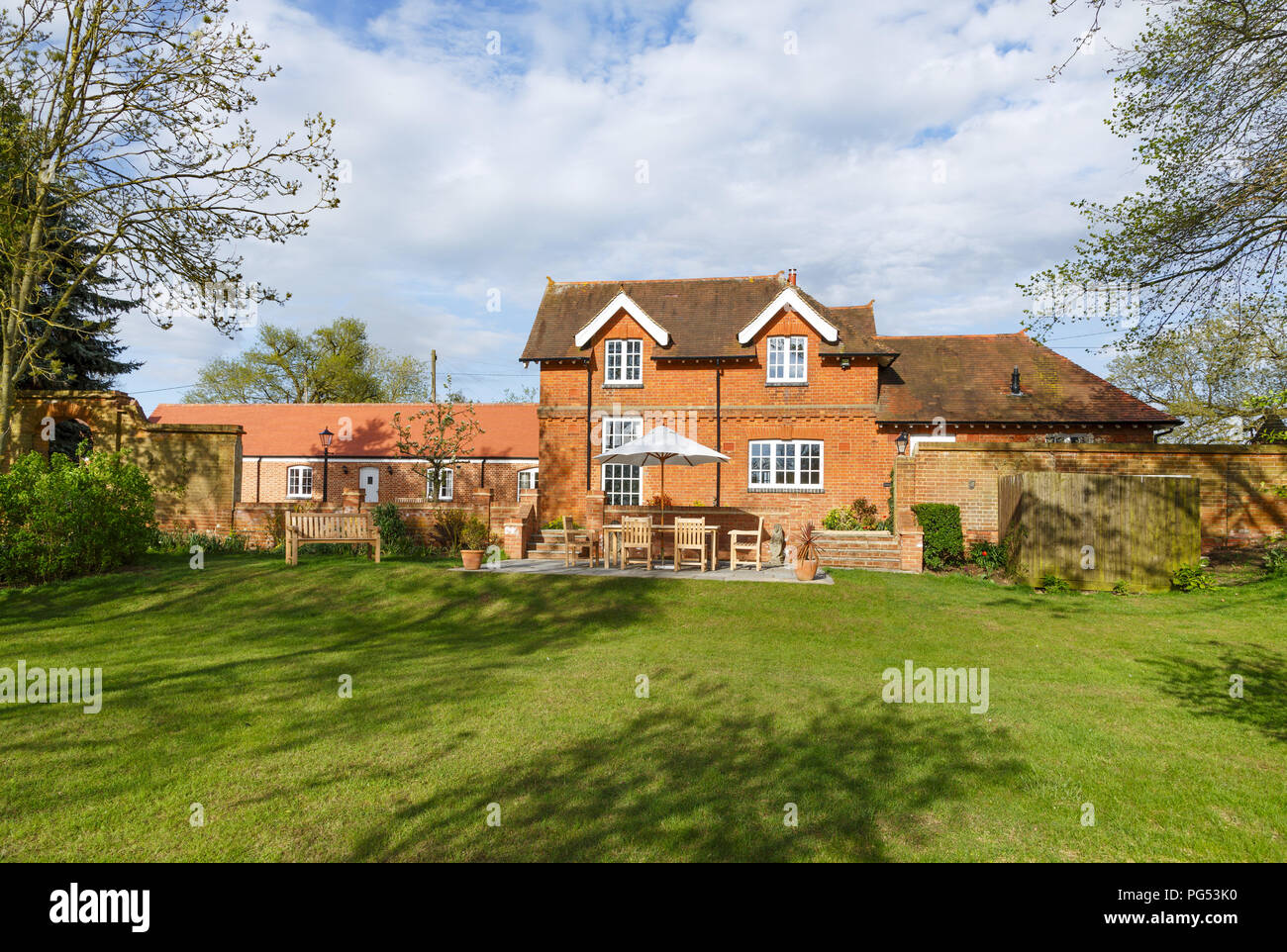 Victorian former coach house and stables with garden and patio. The historic building has been converted into a modern family home - Stock Image
