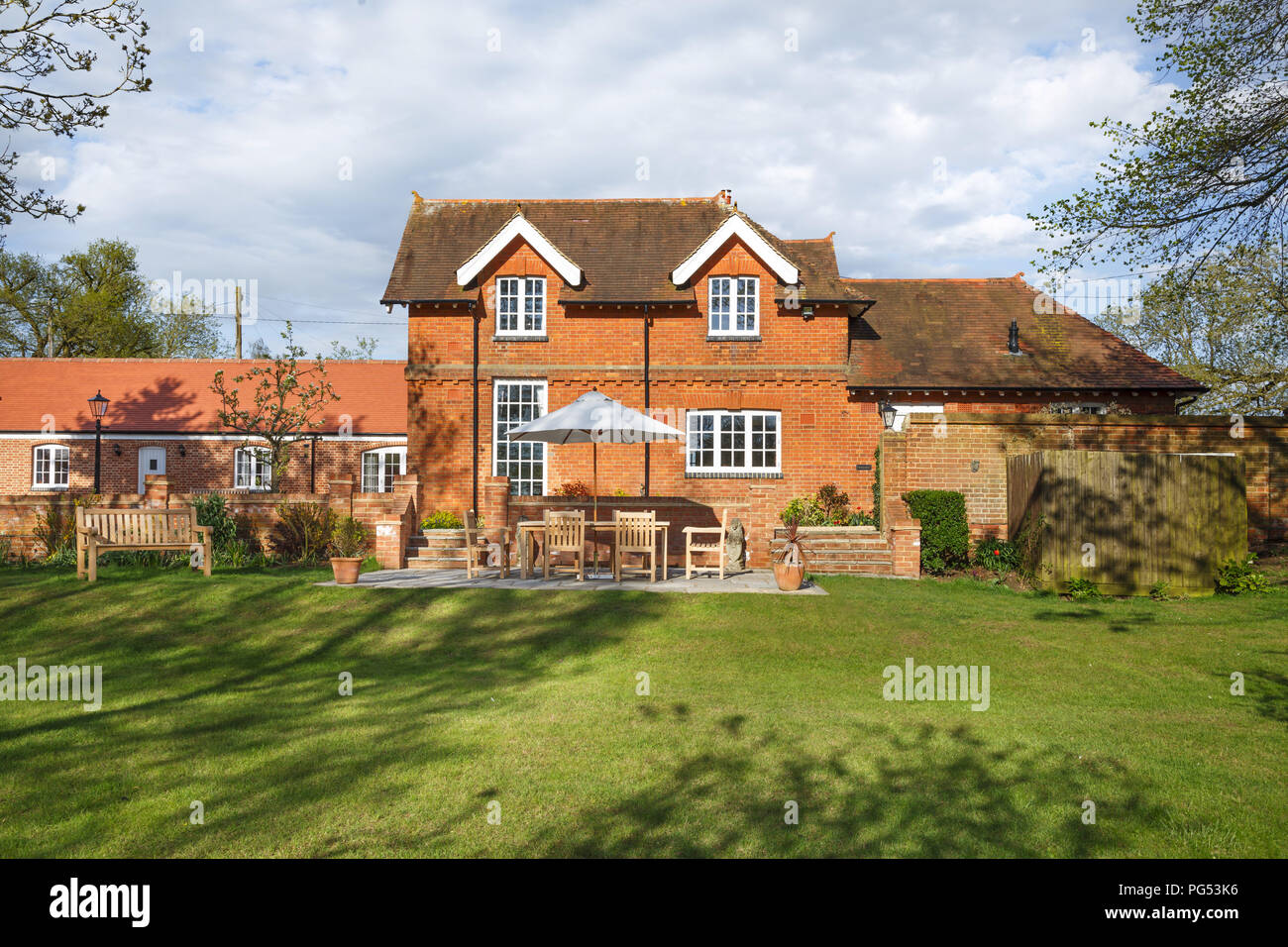 Victorian coach house and stables with garden and patio. The historic building has been converted into a modern family home - Stock Image