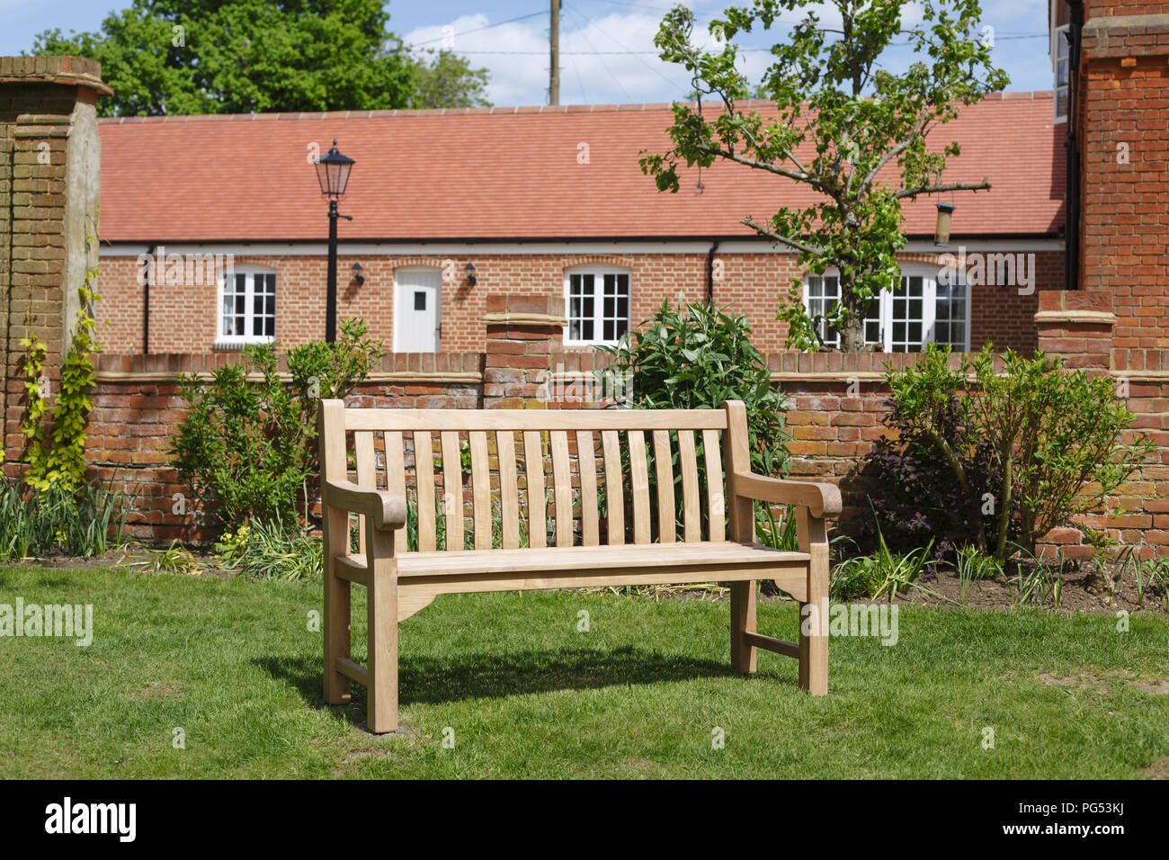 Teak hardwood bench on a lawn in an English garden with historic Victorian home in the background - Stock Image