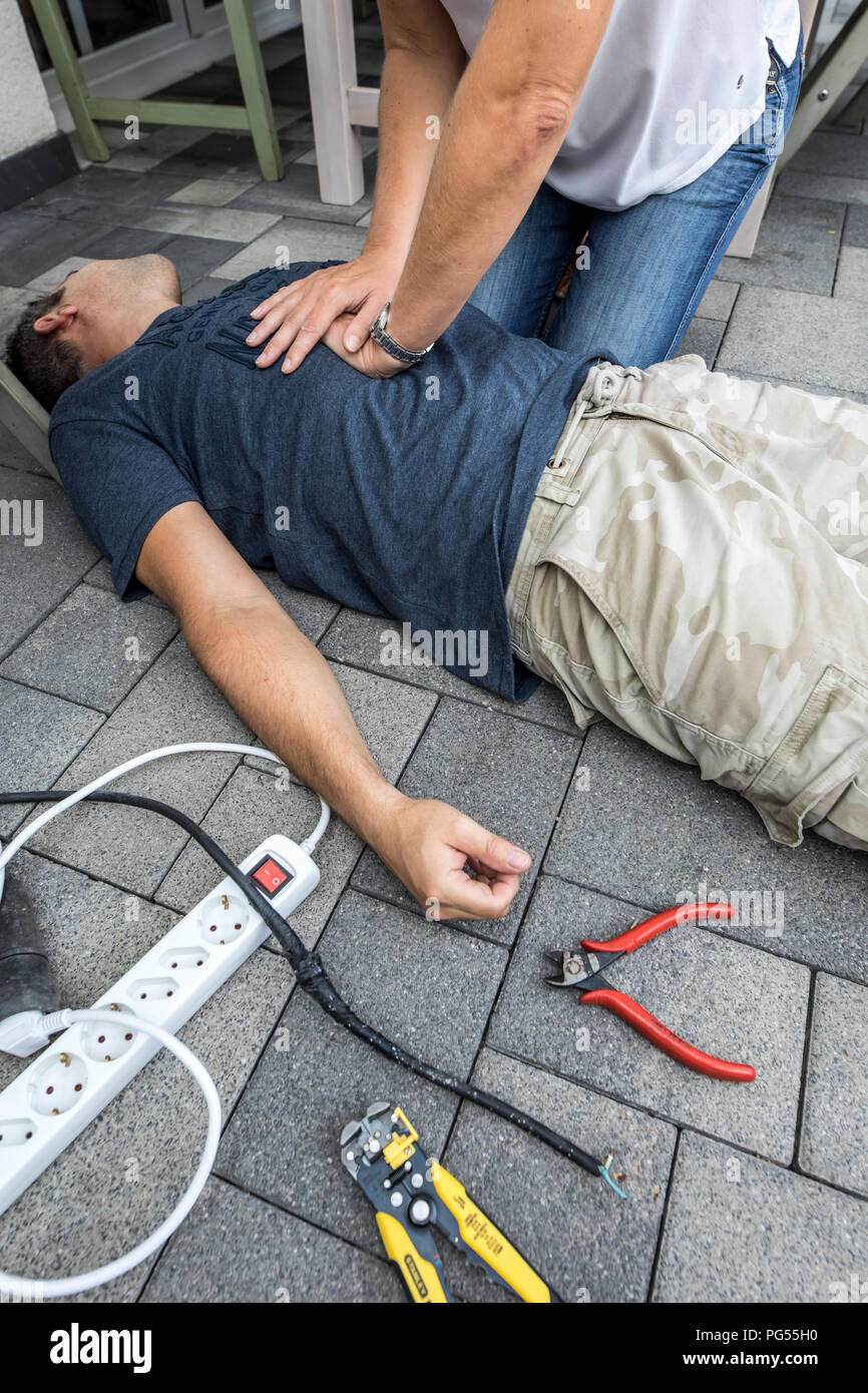 Symbolic picture, first aid, scene posted, resuscitation with a cardiac pressure massage after circulatory collapse caused by an electric short circui - Stock Image