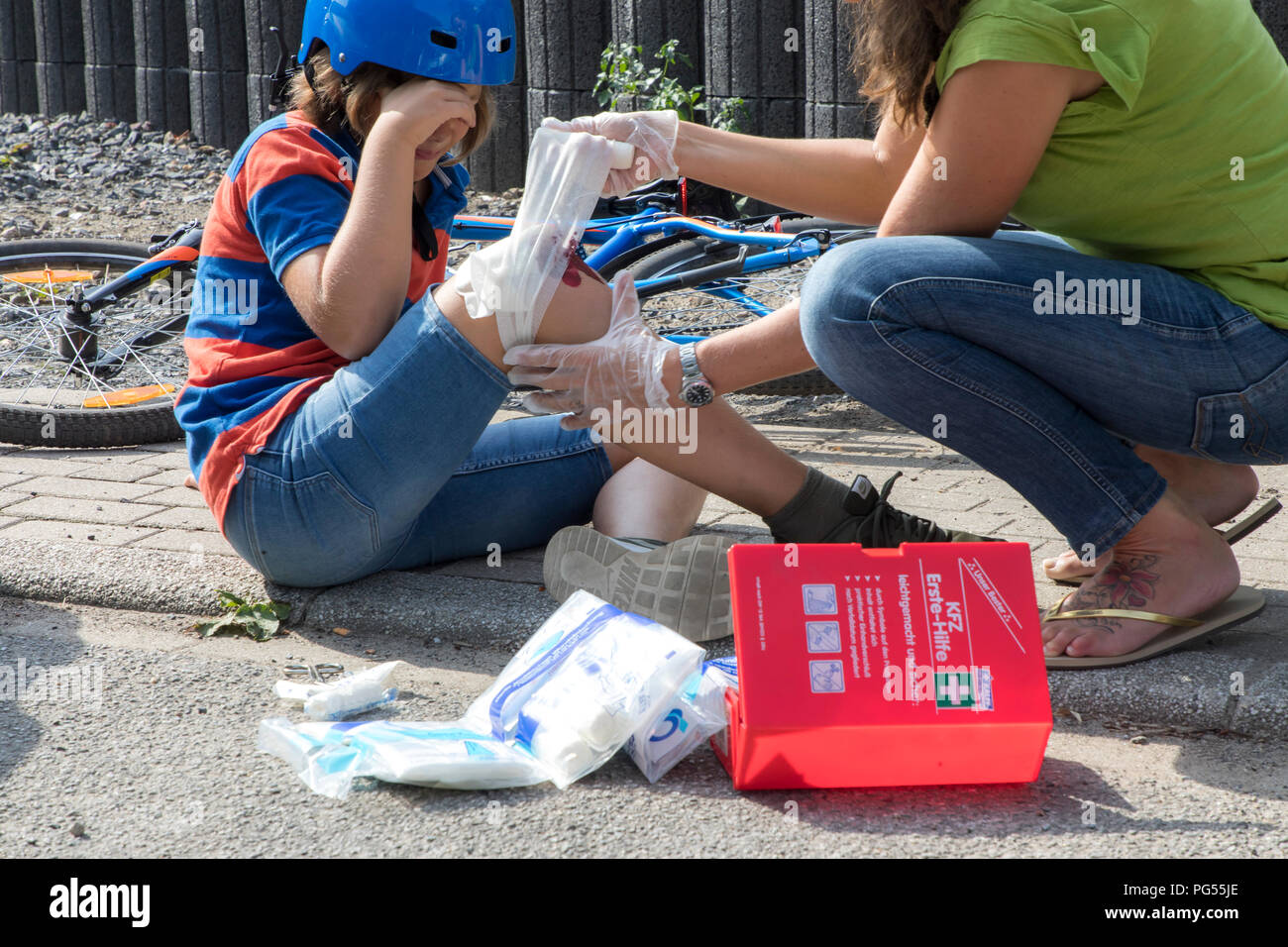 Symbolic photo,  First aid, scene posed, wound care,  after a bike accident, wounded Knee, bandage is created, with bandages from the first-aid box of - Stock Image