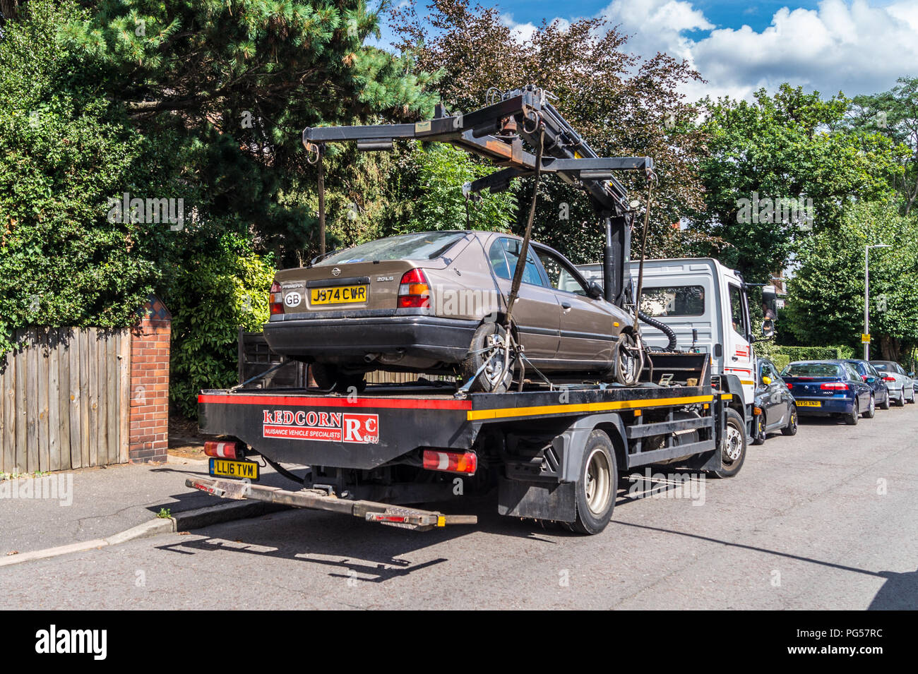 a-1992-nissan-primera-20-lsi-automatic-hatchback-car-being-lifted-onto-a-mercedes-atego-recovery-lorry-for-recycling-south-woodford-london-england-PG57RC.jpg