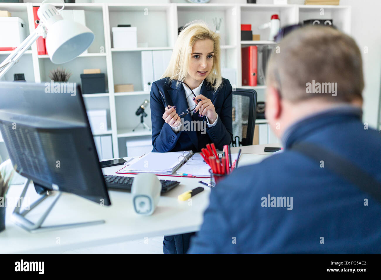 A young girl is sitting at a table in the office, holding glasses in her hand and talking to a man. - Stock Image