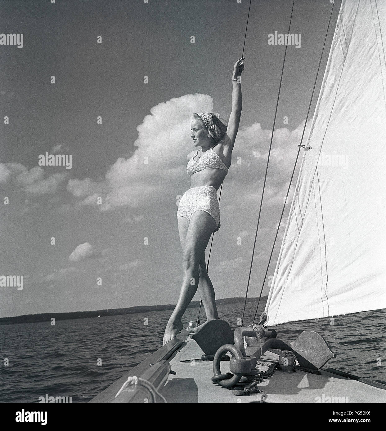 1940s sailing boat. A young woman is aboard a fashionable sailing boat and is standing on deck when it cruises forward with wind in the sails. She is wearing a typical 1940s two piece bathing suit.  Sweden 1946 Photo Kristoffersson ref AC101-4 - Stock Image