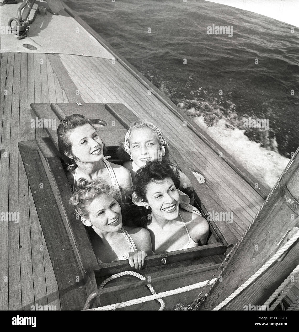 1940s sailing boat. Four young women are enjoying a day at sea on a fashionable wooden sailing boat. They have been below deck and now they are looking up through the hatch and smiles.  Sweden 1946 Photo Kristoffersson ref AC101-5 - Stock Image