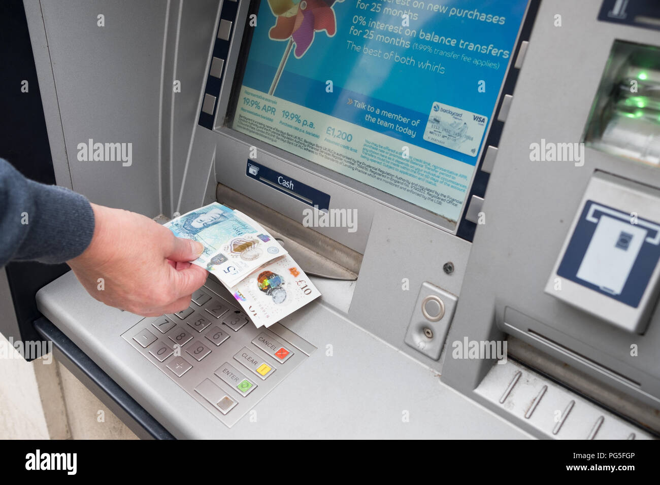 A woman removes £5 and £10 notes from an outside Barclays Bank, hole in the wall, cash point machine Stock Photo