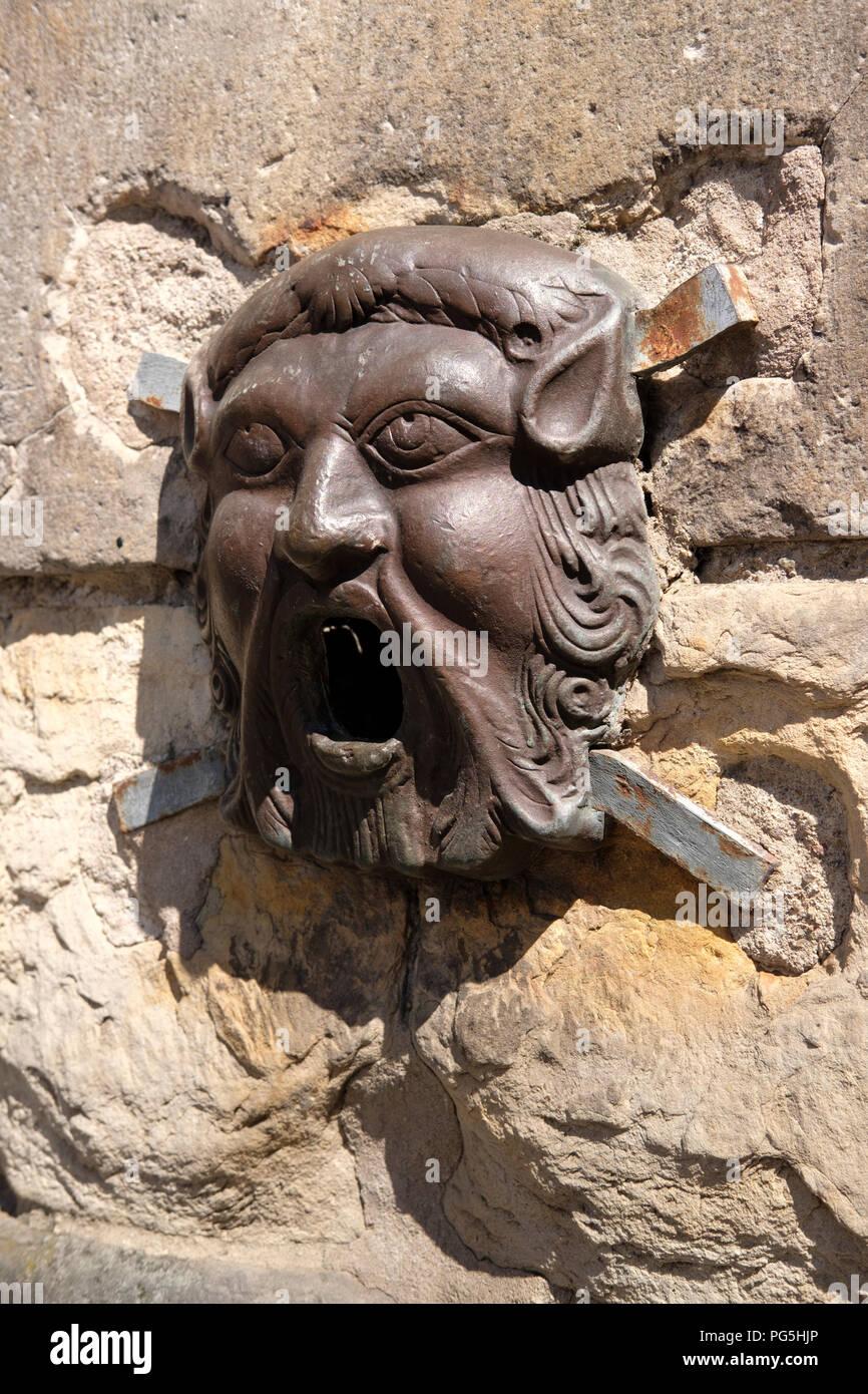 Bronze face on the Netherbow Wellhead, on the Royal Mile, Edinburgh. Stock Photo