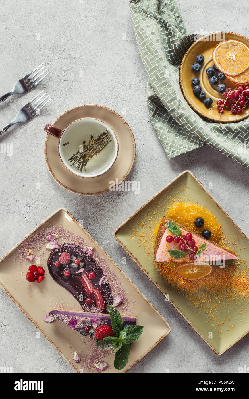 flat lay with sweet carrot cake with berry filling, blueberry cake served with mint leaves and violet petals, cup of herbal tea and cutlery on grey ta - Stock Image