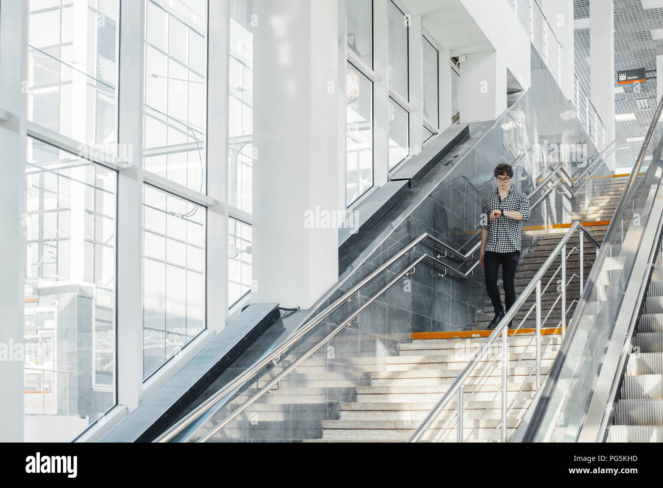 Distant plan of young attractive man going down the stairs in metro station. - Stock Image