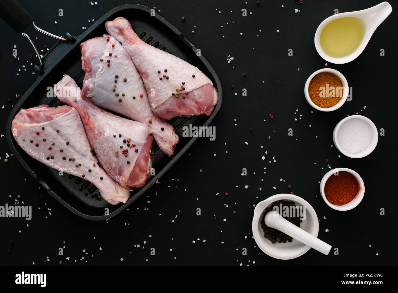 flat lay with turkey legs on grill pan with pepper corns, salt, oil and spices on black table - Stock Image