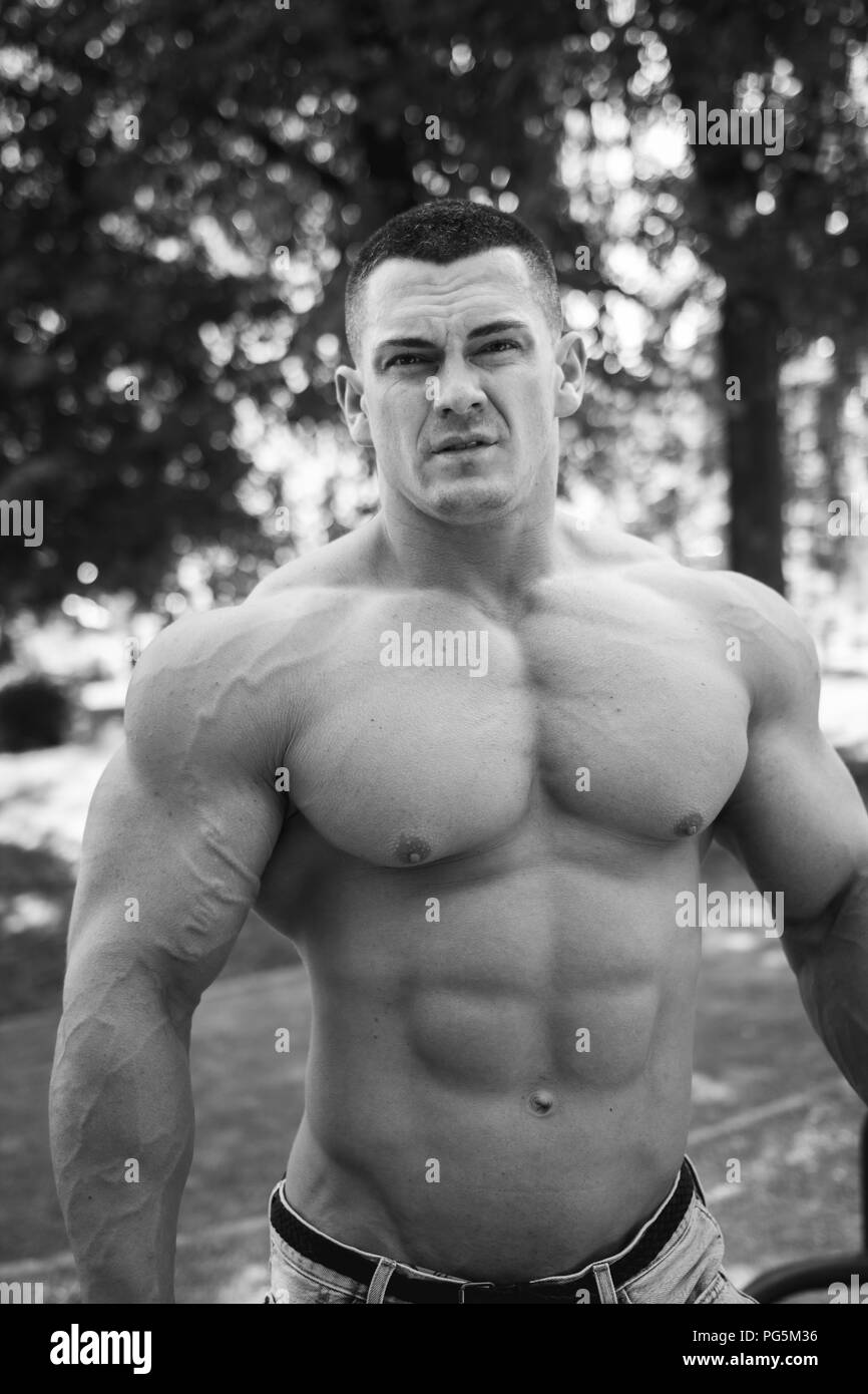 A male bodybuilder stands with bare torso in denim shorts in the park, black and white - Stock Image