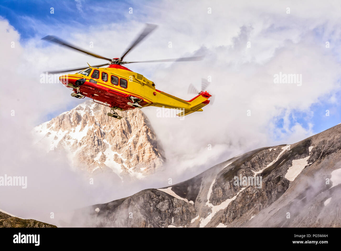 the helicopter of the alpine rescue in a valley of the Gran Sasso - Stock Image