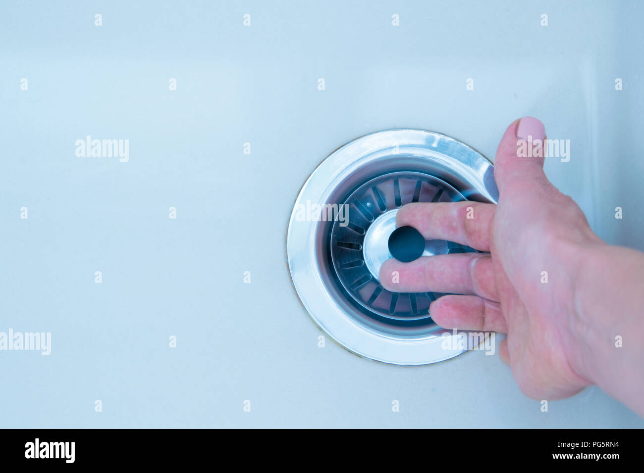 Woman hand pulls close cap of drainage hole of sink to drain water - Stock Image