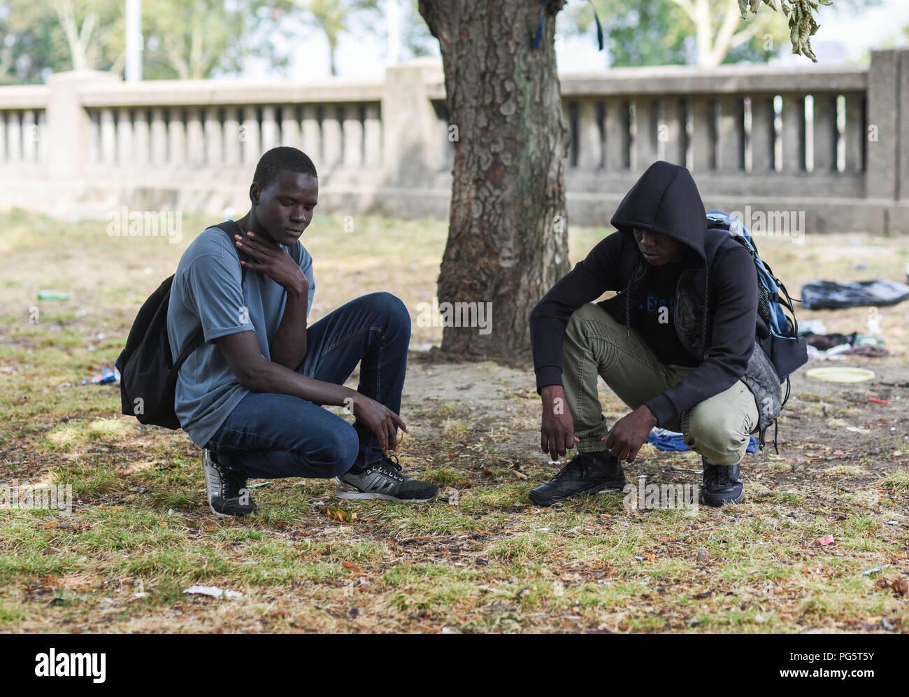 August 14, 2018 - Paris, France: Portrait of two Chadian underage migrants who sleep in a public park near the peripherique (ring road) between porte de la Chapelle and porte d'Aubervilliers. Deux mineurs tchadiens, Samajita (L), 16 ans, et Hassan Bobacar, 15 ans, montrent lÕendroit ou ils dorment en attendant de demander lÕasile. Les deux amis dÕenfance ont quitte ensemble la region du lac Tchad pour echapper aux exactions meurtrieres du groupe jihadiste Boko Haram. *** FRANCE OUT / NO SALES TO FRENCH MEDIA *** - Stock Image