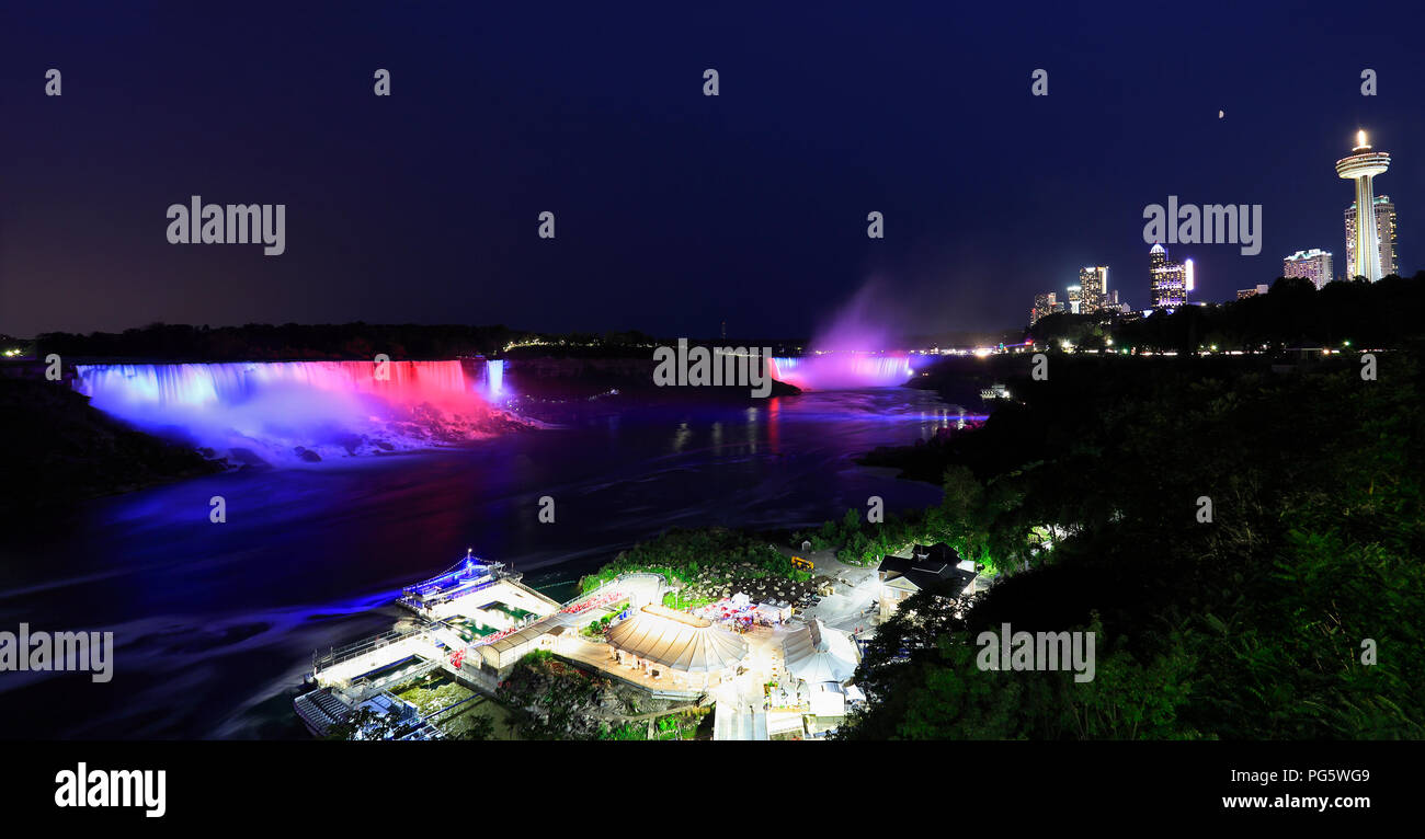 Horseshoe and American Falls, river and Niagara skyline illuminated at night, panoramic view, Canada - Stock Image