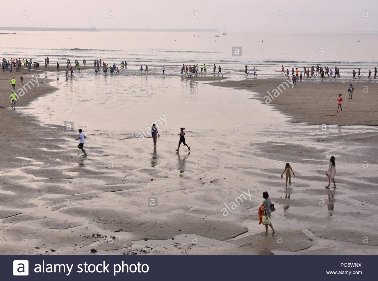 People evening leisure activities misty Atlantic coast. Gijon Asturias Northern Spain Europe. - Stock Image