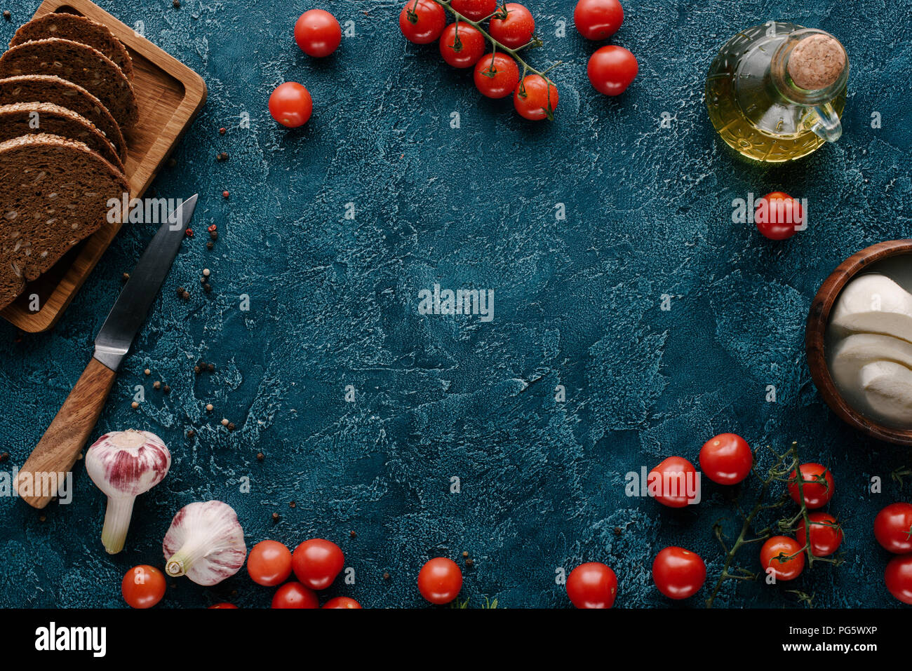 Ripe red tomatoes with bread and spices on dark blue table Stock Photo