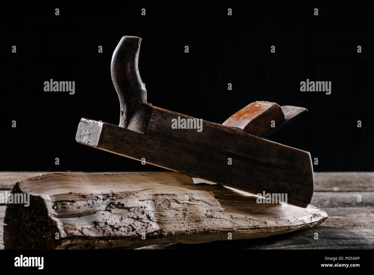 close up view of vintage woodworker plane and stump isolated on black - Stock Image