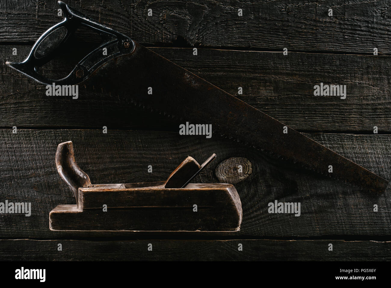 top view of retro rusty saw and woodworker plane on wooden surface Stock Photo