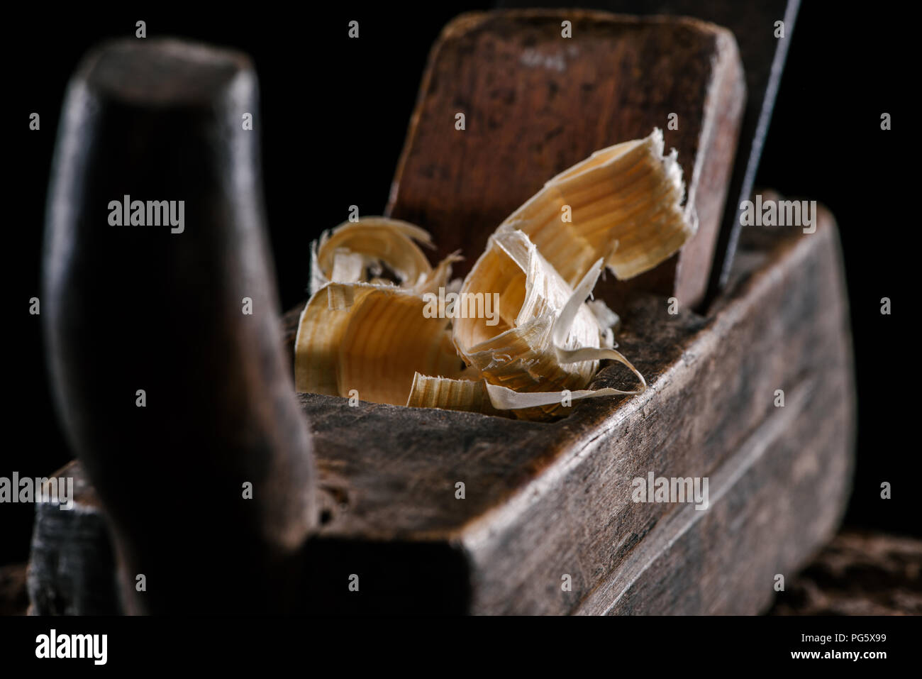 selective focus of vintage woodworker plane and wooden chips isolated on black Stock Photo