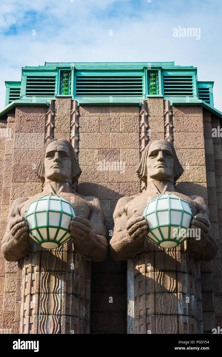 Art Nouveau architecture, view of two huge granite statues holding globe lights sited at the entrance to Helsinki Central Station, Finland. - Stock Image