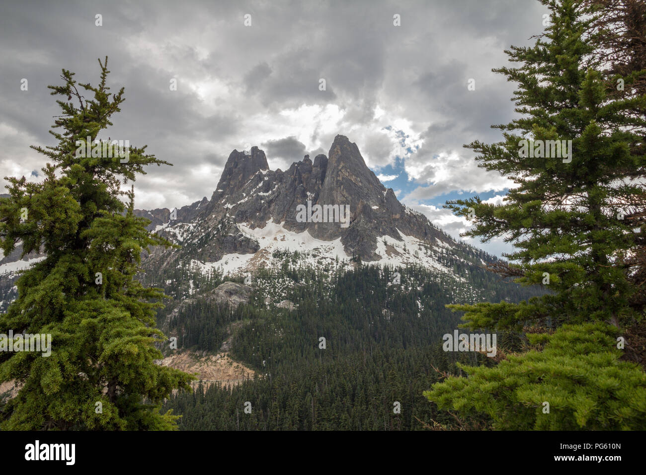 The Early Winters Spires in Washington's North Cascades - framed by conifer trees - in late spring with snow still clinging to the higher slopes - Stock Image
