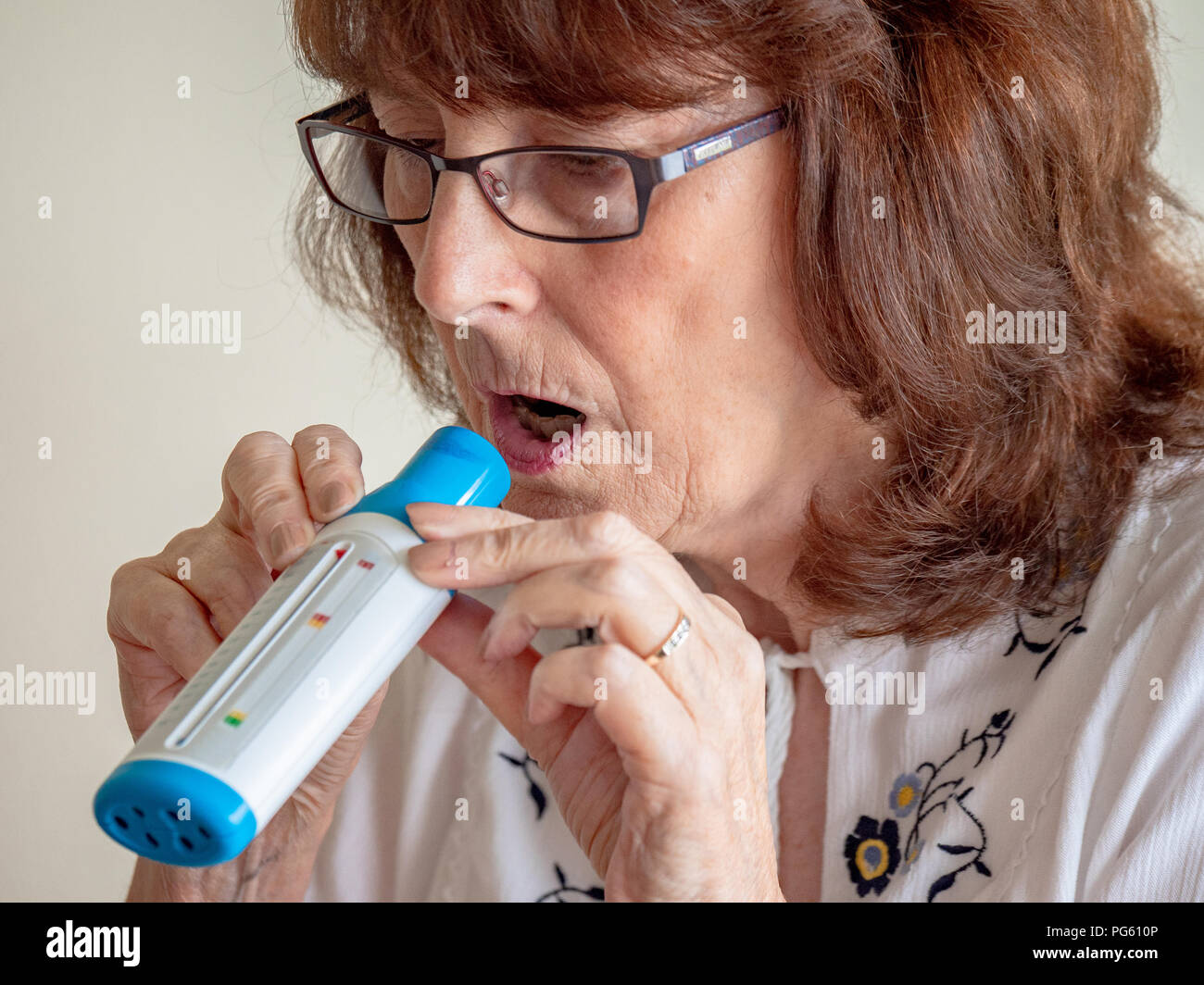 Mature lady blowing into an air flow meter to measure lung function - Stock Image